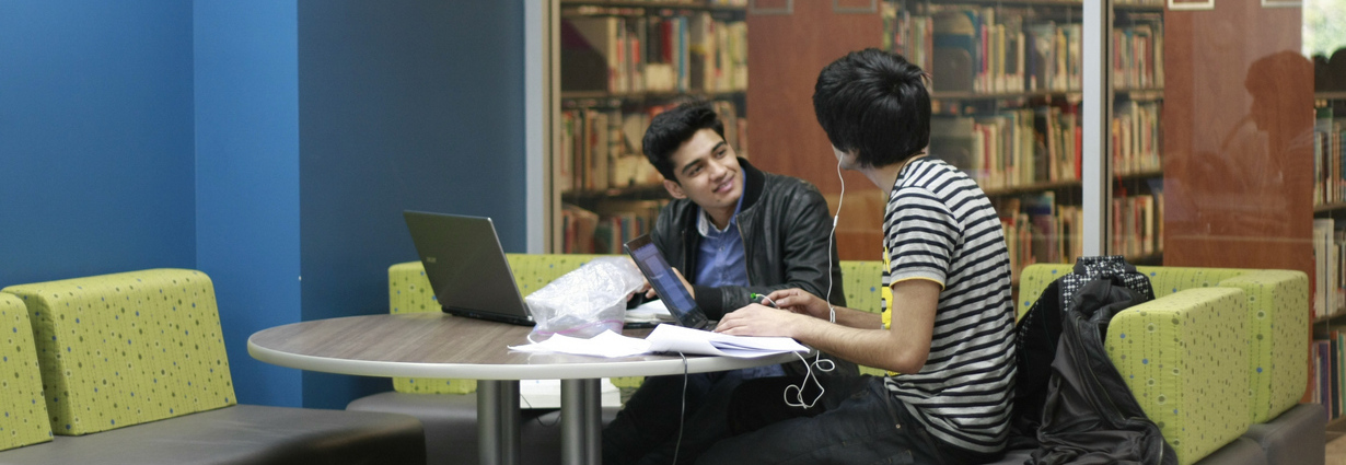 two students with laptops conversing in a SFU Library study space