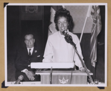photo of Grace McCarthy speaking, Premier W. A. C. sitting in the background