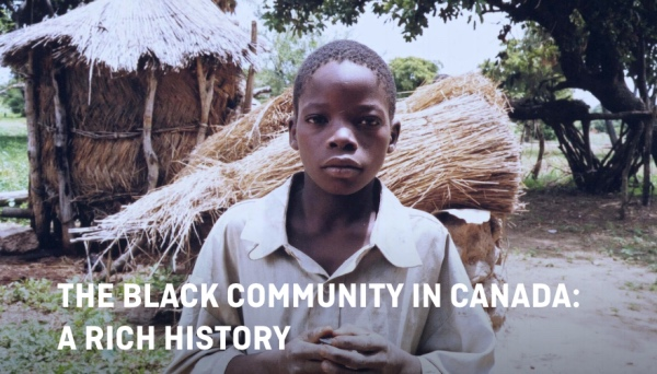 The Black community in Canada: a rich history. A boy looks into the camera, standing in front of a grass hut and a bundle of dried grass.