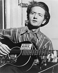 """Woody Guthrie with his guitar, including the sticker, """"This machine kills fascists."""""""