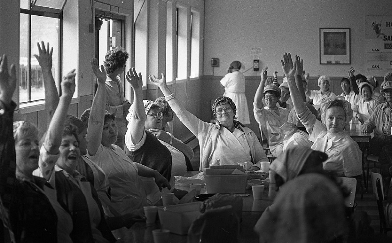 Women sitting at tables in the early 1980s raise their hands during a vote