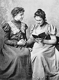 A photograph of Helen Keller with Anne Sullivan, seated with a book.