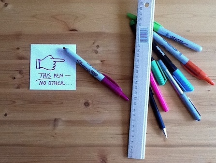 "Image shows several pens and a sticky note pointing to one pen in particular. Text on sticky note reads: ""THIS pen, no other..."" Image demonstrates the grammar rule for non-descriptive adjectives"