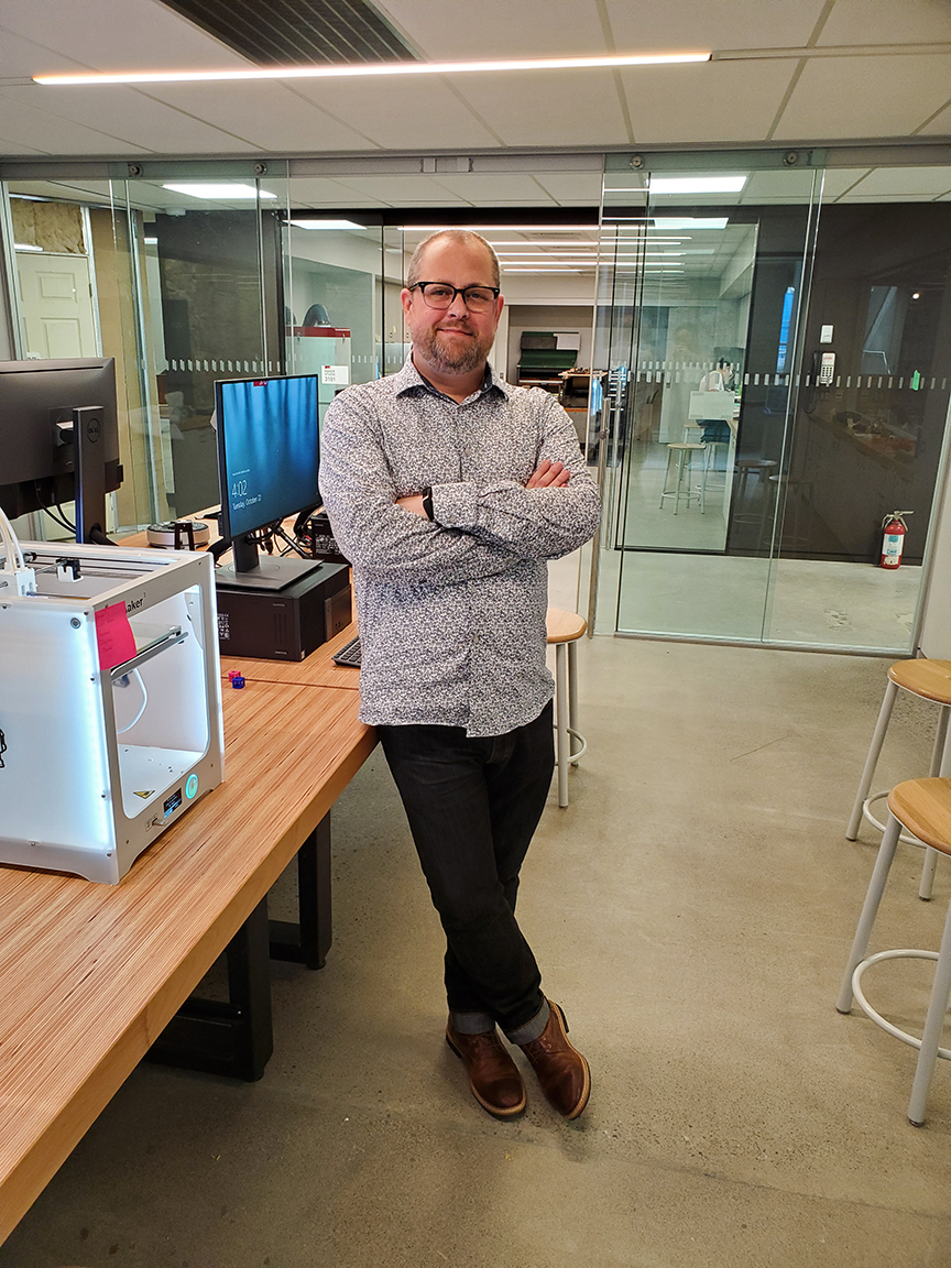 Mikael Kriz, makerspace librarian stands in the new Media and Maker Commons.