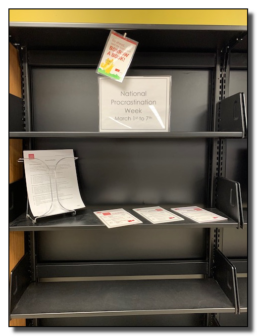 """Picture of empty bookshelves with a sign on the top shelf: """"National Procrastination Week: March 1st to 7th"""""""