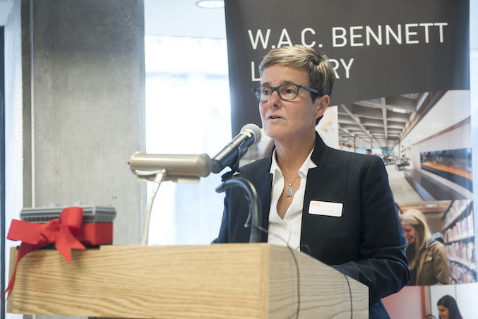 "Gwen Bird stands at a microphone on a podium in front of a banner reading ""W.A.C. Bennett Library."""