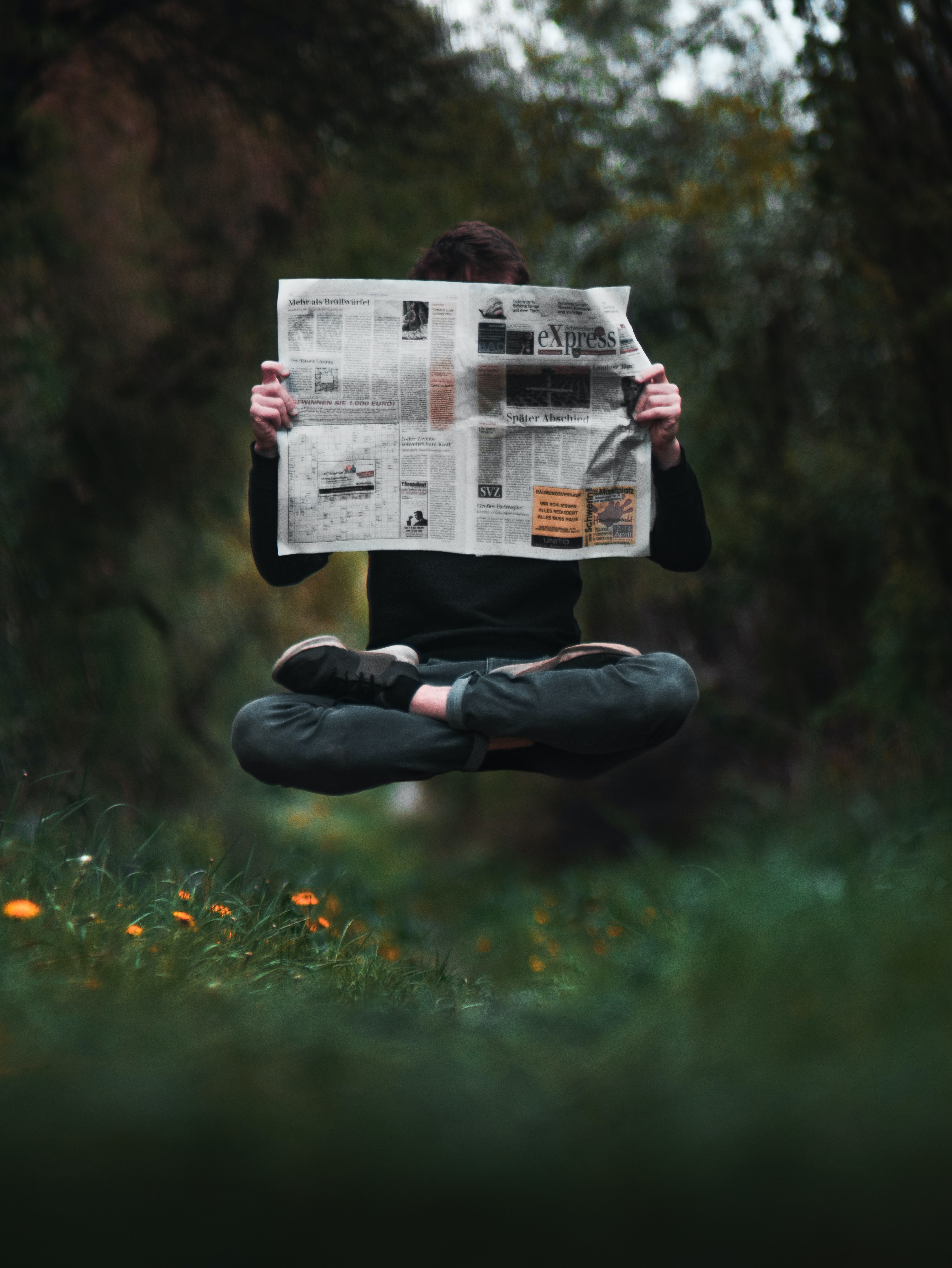 Photo of a cross-legged person reading a newspaper while levitating